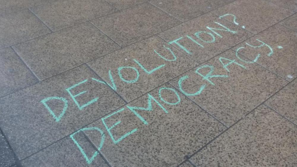 "Message chalked on the pavement outside WYCA meeting, reading ""How might devolution be more democratic?"""