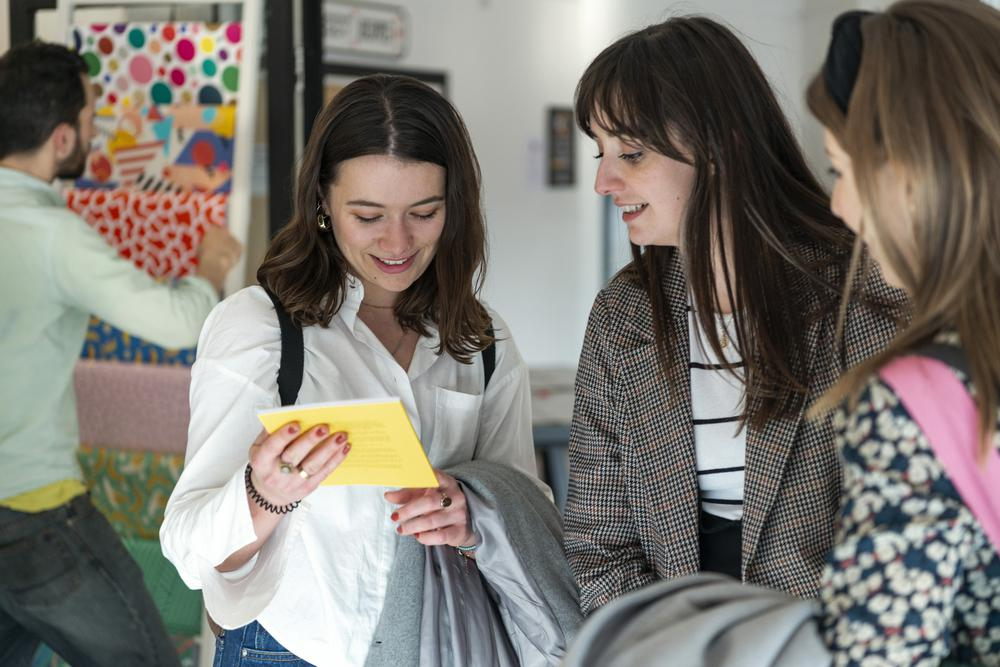 Three young women looking at the cover of the book at the launch event.