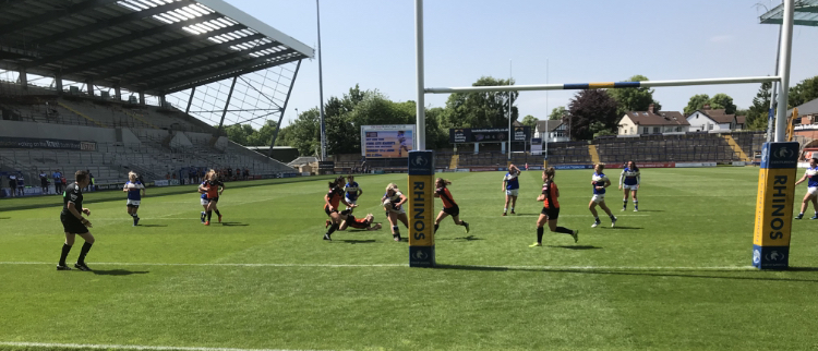 A women's rugby league match underway in a stadium