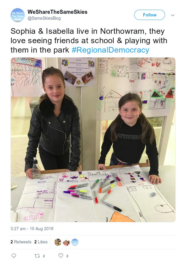 Screenshot of a Twitter post showing two girls in Huddersfield market standing with their hand drawn maps of their neighbourhood